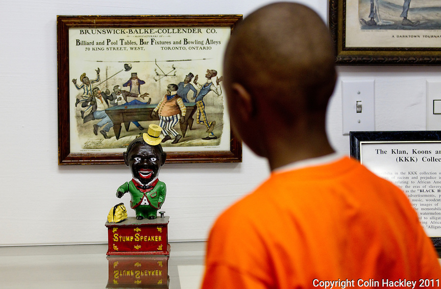 RACISM AND COMMERCE: During a tour of The Black Archives in Tallahassee Jahquaye Hicks, age 8 of Tampa, looks at a coin bank in the Komics, Koon and Klan (KKK) room featuring segregation-era commercial material with racist imagery. .COLIN HACKLEY PHOTO