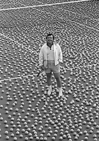 Vic Braden stands amid a sea of tennis balls. Vic Braden Tennis College, Coto de Caza, CA, 1975. Photo by John G. Zimmerman