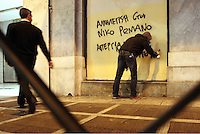 "Pictured: A protester spraying a graffiti reading ""Support to Nikos Romanos"" on a building wall in AThens, Greece Tuesday 02 December 2014<br />