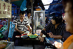 """At the chaotic and smokey Akau Food Court, Indonesians venders cook up Chinese, Malay or Indonesian dishes, on Monday, April 19, 2010. The kiosks also serve as a """"drive-thu"""" window, with motorists requesting their order from their bikes."""