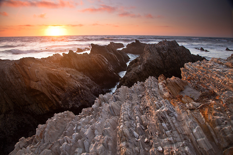 The jagged seacliffs of Montana De Oro SP light up at sunset on the central California coast.