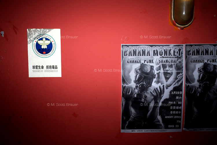 "Posters announce a concert by the Shanghai punk band Banana Monkey at Castle Bar in Nanjing, China. Hanging nearby (left) is a government-sponsored anti-drug poster that says ""Treasure Life, Refuse Narcotics"" in English and Mandarin Chinese."