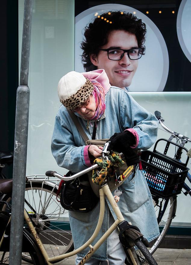 Nederland, Amsterdam, 28 febr 2013.Oude dame zet haar fiets op slot bij een paaltje. .Foto(c): Michiel Wijnbergh