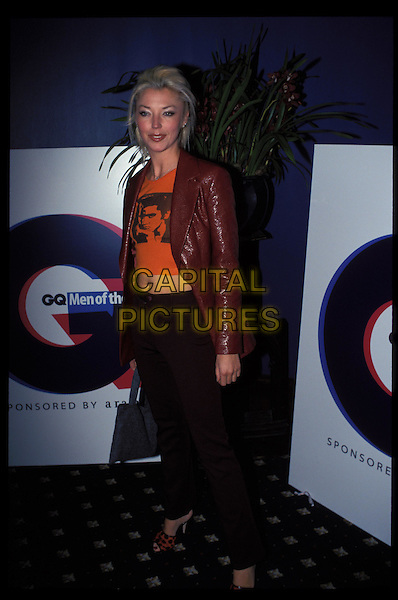 TAMARA BECKWITH.Ref: 7814.red and black polka dot shoes, black trousers, midriff, stomach, orange t-shirt, burgundy jacket, full length, full-length.RAW SCAN - PHOTO WILL BE ADJUSTED FOR PUBLICATION.www.capitalpictures.com.sales@capitalpictures.com.©Capital Pictures.