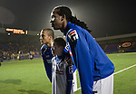 40-year-old former Jamaican international Ian Goodison (right) posing for a photograph with the match mascot after the home team's pre-match warm-up at Prenton Park before Tranmere Rovers host Stoke City in a Capital One Cup third round match. The Capital One cup was formerly known as the League Cup and was competed for by all 92 English Premier League and Football League clubs. Visitors Stoke City won the match 2-0, watched by a crowd of 5,559 spectators.