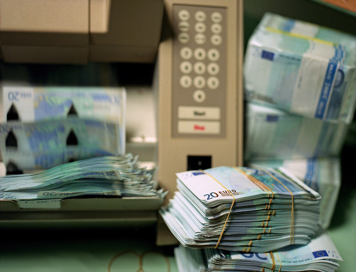 A counting machine and Euro bank notes. The 20 Euro notes are banded into bundles of fifty.
