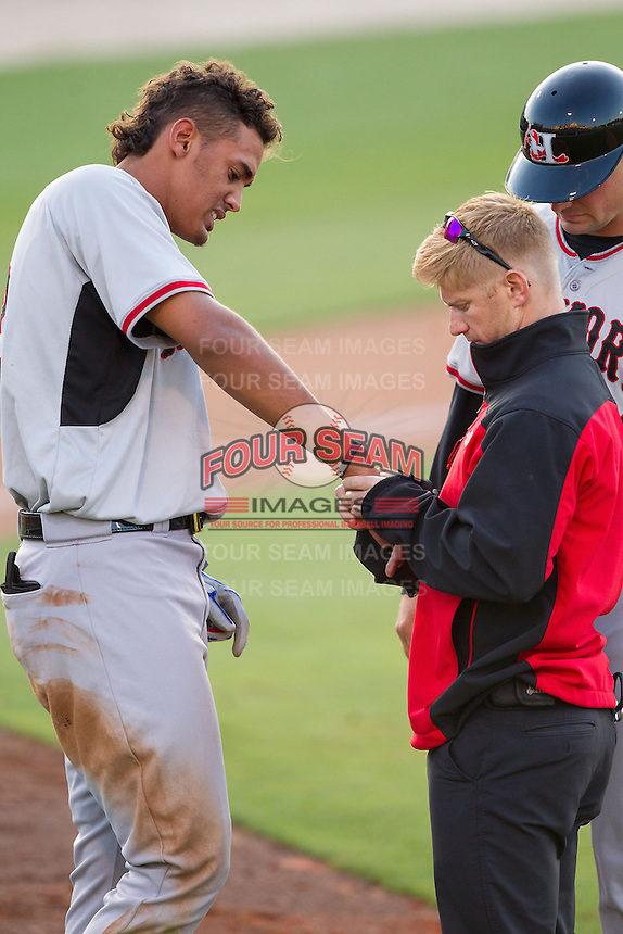 Hickory Crawdads athletic trainer Sean Fields examines the right hand of Ronald Guzman (22) after he was hit by a pitch during the game against the Kannapolis Intimidators at CMC-Northeast Stadium on May 18, 2014 in Kannapolis, North Carolina.  The Intimidators defeated the Crawdads 6-5 in 10 innings.  (Brian Westerholt/Four Seam Images)