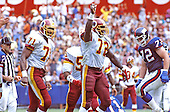 Washington Redskins right defensive end Dexter Manley (72) celebrates a defensive play during the game against the New York Giants at RFK Stadium in Washington, DC on October 2, 1988.  Washington Redskins left defensive end Charles Mann (71) and New York Giants right offensive tackle Doug Riesenberg (72) are also pictured.  The Giants won the game 24 - 23.<br /> Credit: Ron Sachs / CNP