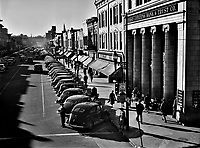 The Long Shadows: Traffic on the main street of Fayetteville, North Carolina at about five o'clock, when the workers start coming out at Fort Bragg, North Carolina. March 1941.<br /> <br /> Photo by Jack Delano.