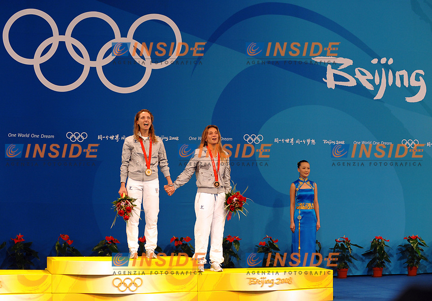 Maria Valentina Vezzali e Margherita Granbassi con le medaglie d'oro e di bronzio vinte nel fioretto, si tengono per mano e cantano l'inno d'Italia.<br /> Fencing hall - Scherma<br /> Pechino - Beijing 11/8/2008 Olimpiadi 2008 Olympic Games<br /> Foto Andrea Staccioli Insidefoto