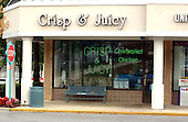 """Montgomery County, MD - October 3, 2002 -- Bullet hole in the window of the """"Crisp & Juicy"""" restaurant in the Leisure World Shopping Center where Sarah Ramos, a 34-year-old babysitter and housekeeper, was fatally shot on 3 October, 2002.  Flowers were left on the bench where Ms. Ramos was sitting when she was killed.<br /> Credit: Ron Sachs / CNP  <br /> <br /> (RESTRICTION: NO New York or New Jersey Newspapers or newspapers within a 75 mile radius of New York City)"""