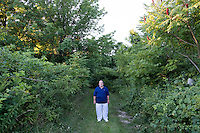Dr. Amjad Bahnassi is the Chairman of the Board of the Islamic Society of Greater Worcester, seen here in Dudley, Massachusetts, on Tues., Aug 23, 2016, on a road leading to a plot of land that the Islamic Society is trying to buy to create a Muslim cemetery for the community. The nearest Muslim cemetery is in Enfield, Connecticut, and many of the group's relatives are buried there. The group is looking for a place closer to Worcester to bury their loved ones but has encountered substantial opposition from locals and town officials. Bahnassi is a psychiatrist and Medical Director of Behavioral Healthcare Services and in Worcester, Massachusetts. He is a Syrian immigrant who arrived in Worcester in 1983 for a residency at the University of Massachusetts. He became an American citizen in the late 1980s. His son is buried in the Enfield, Connecticut, Muslim cemetery, and he says the distance to that cemetery makes it difficult to visit his son's gravesite as often as he would like. He believes Dudley locals' fear of and bigotry toward Muslims is driving opposition to the proposed cemetery.