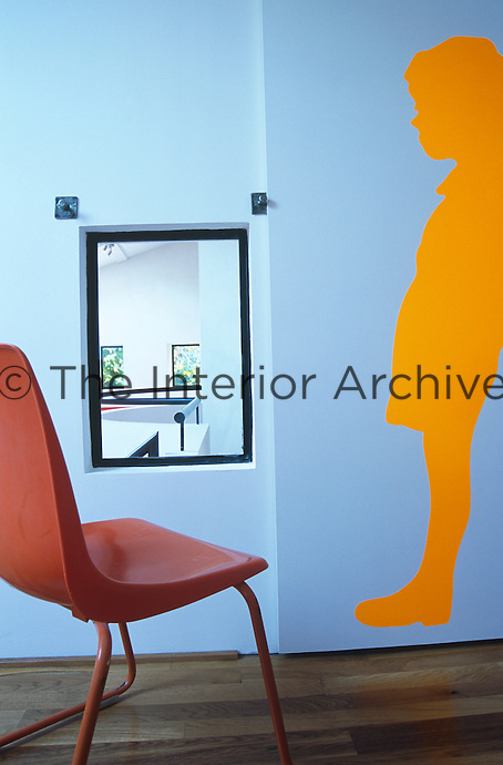 A yellow adhesive silhouette of a boy adorns the wall of this children's bedroom