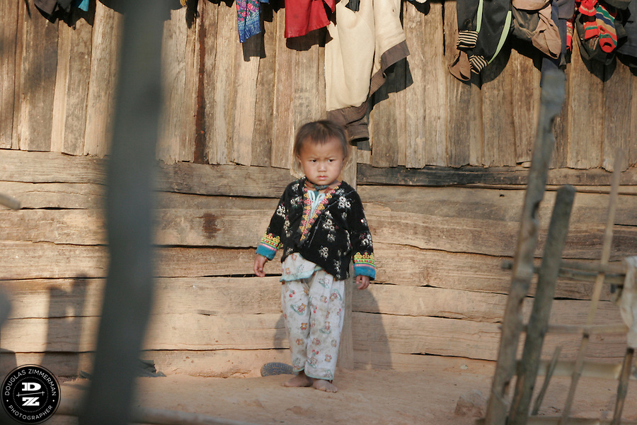 A young child walks through the village of Sam Yord, in the county of Louang Namtha,  Laos.  The remote village, only accessible on foot is a village of the Hmong ethnic group. Photograph by Douglas ZImmerman.