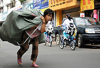 A woman carries goods on the back in Haikou in island province of Hainan, China..30 Oct 2008