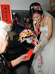 Taiwanese Wedding -- The bride offers her father a red envelope ('hong bao') to thank him for raising her.