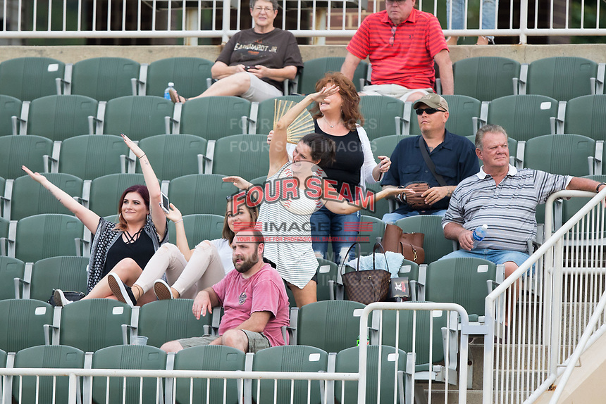 """Fans dance along with """"Y.M.C.A."""" between innings of the South Atlantic League game between the Greensboro Grasshoppers and the Kannapolis Intimidators at Kannapolis Intimidators Stadium on August 13, 2017 in Kannapolis, North Carolina.  The Grasshoppers defeated the Intimidators 3-0.  (Brian Westerholt/Four Seam Images)"""