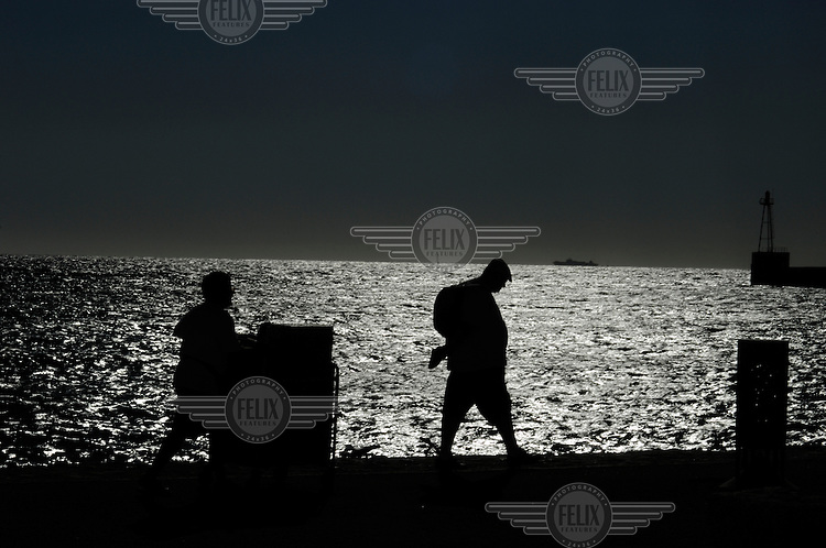 A large man walking by the Mediterranean pursued by a hopeful snack seller pushing his stand.