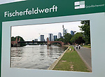 Germany-Frankfurt/Main - June 16, 2018 -- On the banks of river Main, information panel on the historic site of Fischerfeldwerft, with modern skyline of the financial district in the back -- Photo © HorstWagner.eu