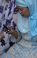 Muslim women communicating with her cellphone,Manila, Philippines