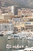 A view of Monte Carlo harbour with luxury motor yachts and speedboats.