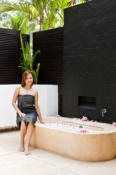 Woman prepares for a floral milk bath in the outdoor bathing area of the spa treatment suite at Visaya Spa, FCC Angkor, Siem Reap, Cambodia.