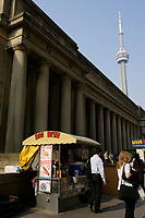 People going to work , early in the morning, walk beside a hot dog stand, on Front street  in downtown Toronto.<br />