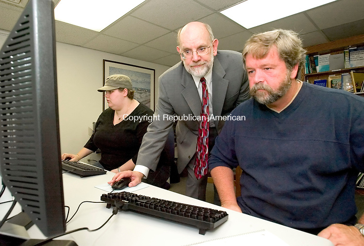 WATERBURY, CT-- 24 SEPTEMBER 2007--092407JS01-John Long, center, program officer for the Nonprofit Assistance Initiative, a joint project of the Connecticut Community Foundation and the United Way of Greater Waterbury demonstrates an online grant search to Mike Arsenault, right, president of Mission Greater Waterbury and Gina Salerno, left, of the Naugatuck Historical Society Museum, at the opening of the Nonprofit Assistance Initiative Resource Center in Waterbury on Monday. The center, located at the Connecticut Community Foundation office on 43 Field Street in Waterbury, is open Monday through Friday from 9 a.m. to 5 p.m. and offers two databases for grant research, a library of books about nonprofit management, and information about services for area nonprofit. <br /> Jim Shannon / Republican-American