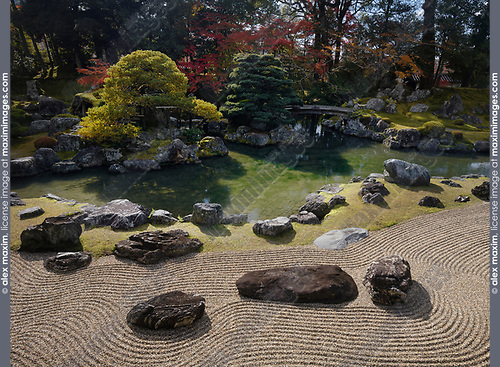 Autumn scenery of a traditional Japanese Zen rock garden with Kamo no Sanseki stones in front of a pond with bridges leading to islands Kameshima and Tsurushima with old white pine trees growing on them. Sanbo-in, Sanboin Buddhist temple, a sub-temple of Daigo-ji temple, Daigoji complex in Fushimi-ku, Kyoto, Japan 2017 Image © MaximImages, License at https://www.maximimages.com