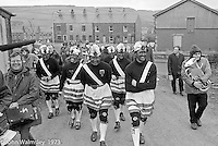 """The """"Nutters' Dance"""", Bacup, Lancashire  1973.  On Easter Saturday every year the """"Coco-nut"""" dancers gather at one boundary of the town and dance their way across to the other accompanied by members of the Stackstead Silver Band, collecting for charity as they go.  Here they're taking a break and walking to the next spot."""
