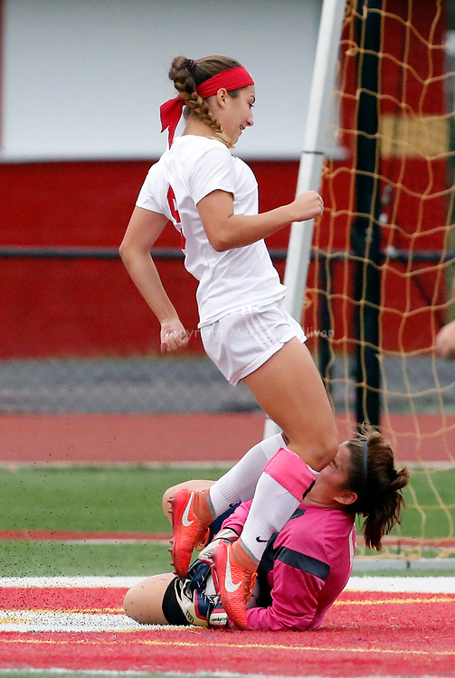 Dunellen at Edison girls soccer in a GMC Tournament game held at Edison High School on Thursday October 20, 2916.<br /> Dunellen goalie # 0 (lower) Karina Camera is kneed in the face by Edison's # 9 (left) Felicia Forsythe as Camera dives to make the save of the shot attempt on goal.