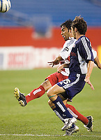 FC Dallas' Carlos Ruiz chips the ball over goalkeeper Matt Reis and over the net while being marked by Michael Parkhurst of the Revolution. The New England Revolution defeated FC Dallas 3 to 2 at Gillette Stadium, Foxbourgh, MA, on July 16, 2005.