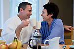 Mature couple, holding coffee cups, face to face