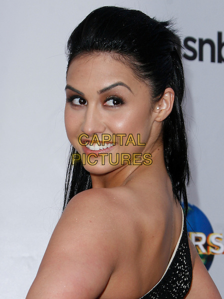 LAUREN GOTTLIEB . arriving at the The Cable Show 2010 To Feature An Evening With NBC Universal held at  Universal Studios Hollywood in Universal City, California, USA, .May 12th, 2010..portrait headshot looking back over shoulder smiling  black lace one shoulder .CAP/ROT/AMB.©Adriana M. Barraza /Roth Stock/Capital Pictures