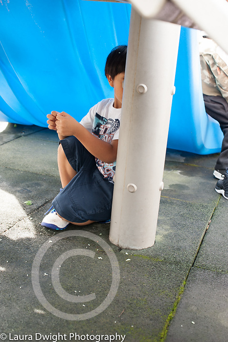 Education preschool outside playground game of hide and seek, boy hiding under playground equipment
