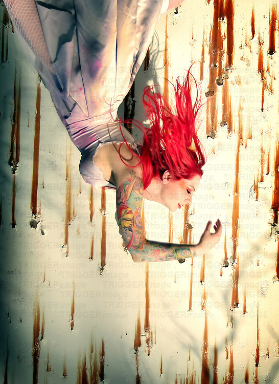 A woman with bright hair, a tattered dress, and lots of tattoos hangs upside-down like she is falling.