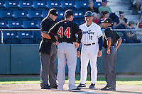Everett AquaSox manager Dave Valle #10 meets with Vancouver Canadians manager John Schneider #44 and umpires Benjamin Bayer and Kale Rodrigues prior to a game at Everett Memorial Stadium in Everett, Washington on July 9, 2014.  Everett defeated Vancouver 9-4.  (Ronnie Allen/Four Seam Images)