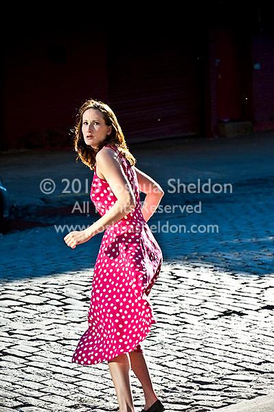 Woman running across cobblestone street, rear view
