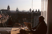 Prague, Czech Republic. Man reading a newspaper in a rooftop restaurant with a view over the old city.