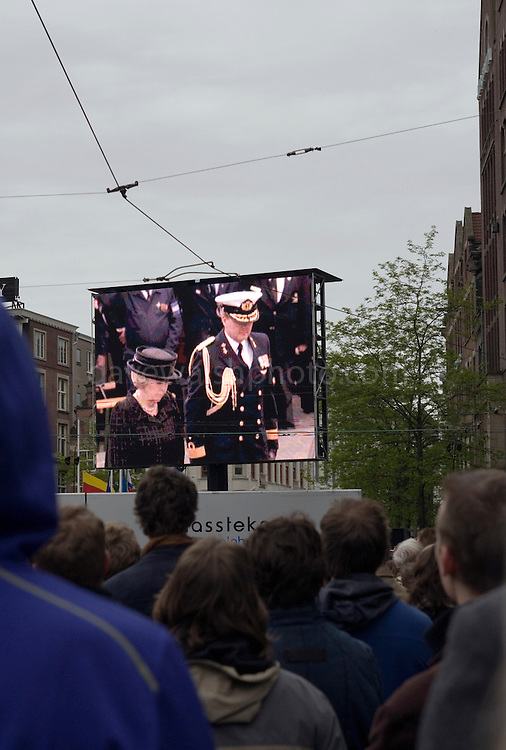 Queen Beatrix and Crown Prince Willem-Alexander appear in front of the crowd on a massive TV on Dam Square  during a WW2 Remembrance Day Ceremony in Amsterdam May 4th 2009. The Dutch Queen Beatrix attended, under heavy security and sniper cover following an attempted attack on the Royal Family on Queens Day in Apeldoorn.
