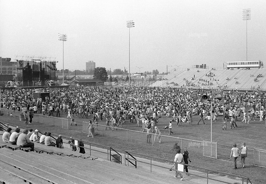 The Grateful Dead Concert at Dillon Stadium from far back left side of the Venue. 31 July 1974. Before the show starts and much of the audience has yet to arrive. Photograph taken with a Nikon FTn Camera, 35mm lend with 35mm Kodak Tri-X B&W film.