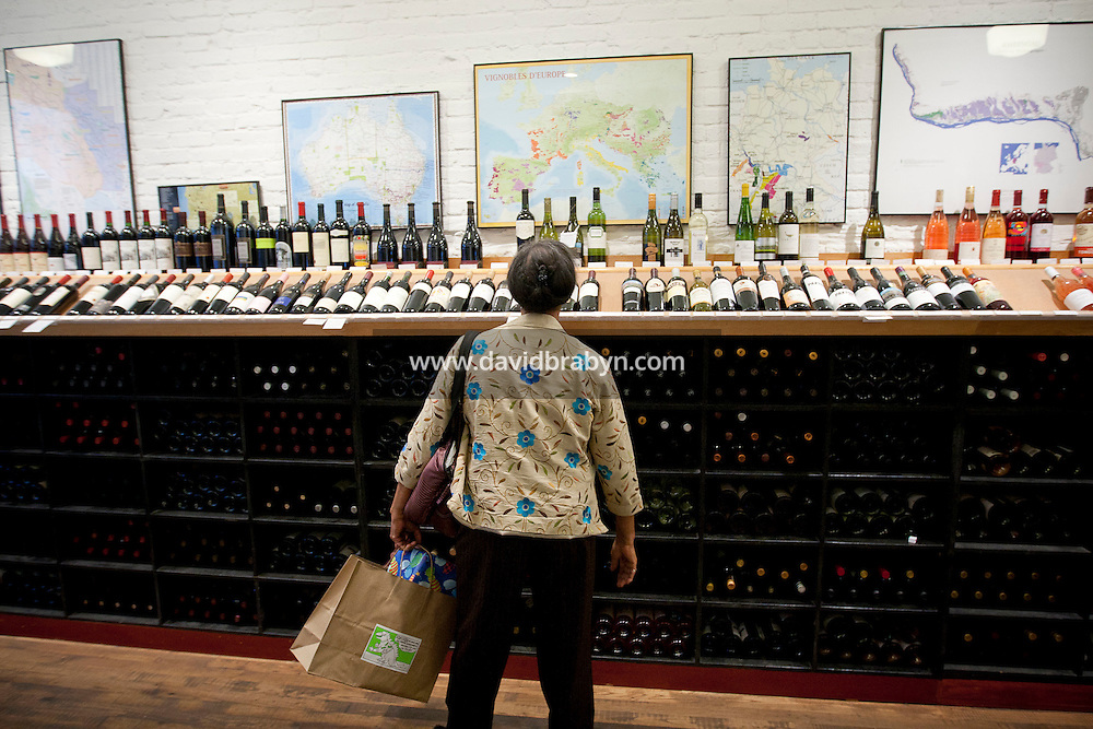 A woman looks at wines on shelves at Chambers Street Wines in New York, NY, USA, 22 May 2009. The store specializes in naturally made wines from artisanal small producers and has received a Slow Food NYC Snail of Approval.