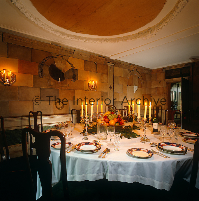 This Georgian dining room has walls of trompe l'oeil brick and a circular plasterwork ceiling ornamentation which reflects the shape of the dining table