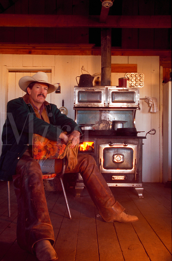 Portrait of a cowboy sitting in his cabin with an old-fashioned stove in the background.