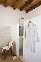 The walk-in shower is separated from the rest of the bathroom by a whitewashed stone partition