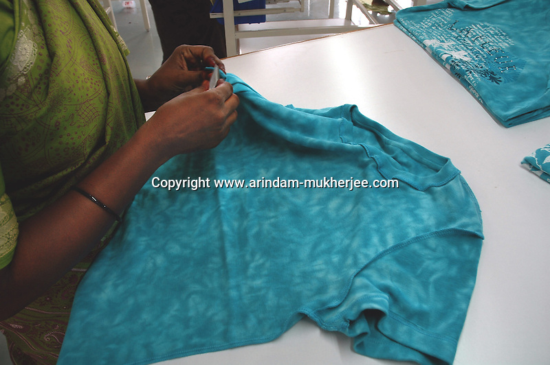 An Indian lady finaly chcking the finished products  at Srinidhi's garment stitching factory in Tirupur, Tamilnadu. After lifting of quota system in textile export on 1st january 2005. Tirupur has become the biggest foreign currency earning town of India.