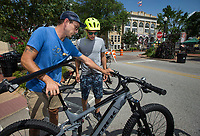 NWA Democrat-Gazette/BEN GOFF @NWABENGOFF<br /> Luke Hall (left) with Bike NWA shows Jean Baerga of Sheridan, Ind. how to use the dropper seat post on an electric mountain bike Friday, July 5, 2019, during First Friday on the Bentonville Square. Bike NWA partnered with Phat Tire Bike Shop to provide the e-bikes for guests to try out.