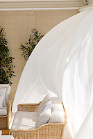 Adriatic wind blows the long white curtains that surround the outdoor living room on the covered terrace