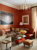 Tones of orange and brown give the sitting room a warm ambience. The custom made daybed and Art Deco armchair are covered in a Pierre Frey fabric the 1960s Italian chandelier is from John Salibello and the carpet is by Stark; the photograph is by Tim Davis and the print is by Damien Hirst.