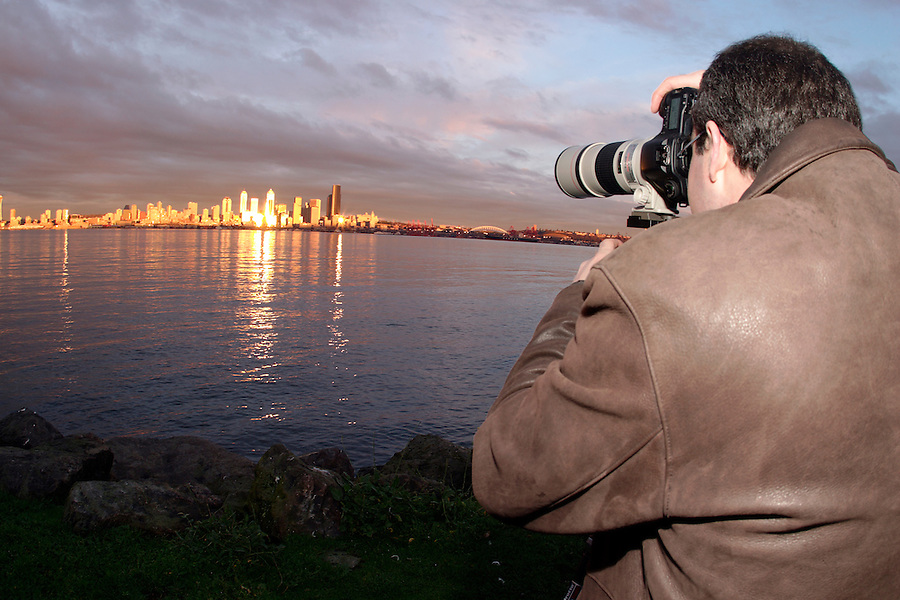 Man photographing Seattle skyline reflecting in Elliot Bay from West Seattle, Seattle, Washington, USA